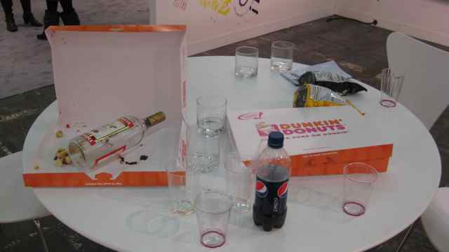Table at the booth of Paul Kesmin Gallery with Dunkin' Donuts, Pepsi and Stolichnaya