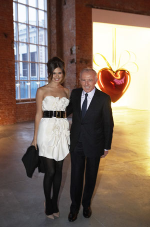 Daria Zhukoava and François Pinault at the Opening Night (Jeff Koons' Hanging Heart in the background), Via Saatchi Gallery