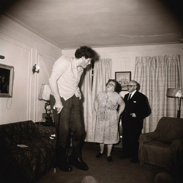 A Jewish giant at home with his parents in the Bronx, N.Y.C.  1970 Diane Arbus