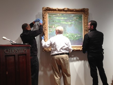 Art handlers installing the Monet painting