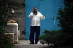 Chinese dissident artist Ai Weiwei talks on his mobile phone as he walks near the entrance to his studio in Beijing, via David Gray for Reuters
