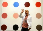Damien Hirst with a Spot Painting, via The Independent