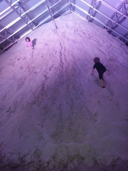 Children playing on the massive sand installation at Design Miami