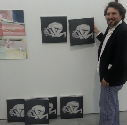 Gallerist Federico Luger with copies of a Yue Minjun, created by Gabrielle Di Matteo via Art Observed Staff