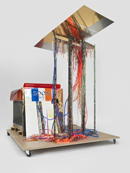 "Isa Genzken. Disco Soon (Ground Zero), 2008. Synthetic polymer paint on plastic, cardboard, mirror, spray paint, metal, fabric, hose lights, mirror foil, printed sticker, wood blocks, fiberboard, and casters. 86 1/4 x 80 11/16 x 64 15/16 "" (219 x 205 x 165 cm). Carlos and Rosa de la Cruz Collection. Courtesy the artist and Galerie Buchholz, Cologne/Berlin. © Isa Genzken"